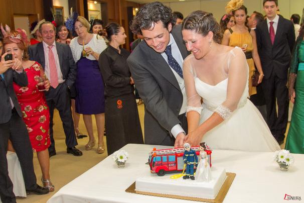Los recién casados cortan una especial tarta de boda en fondant