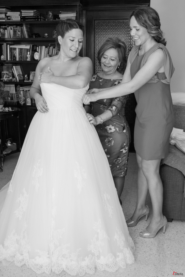 La madre y la hermana de la novia la ayudan a vestirse