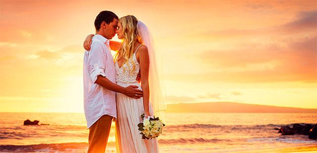 Pareja de novios durante su boda en la playa