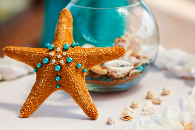 Decoración de bodas en la playa con estrellas de mar y caracolas