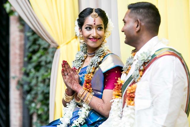 Pooj & Siva se miran enamorados durante la ceremonia de la boda tradicional hindú