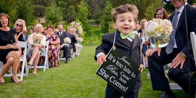 Niño andando con un cartel por el pasillo de la ceremonia de boda