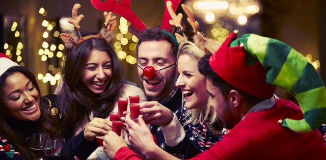 Personas divirtiéndose en la comida o una cena de empresa en Navidad