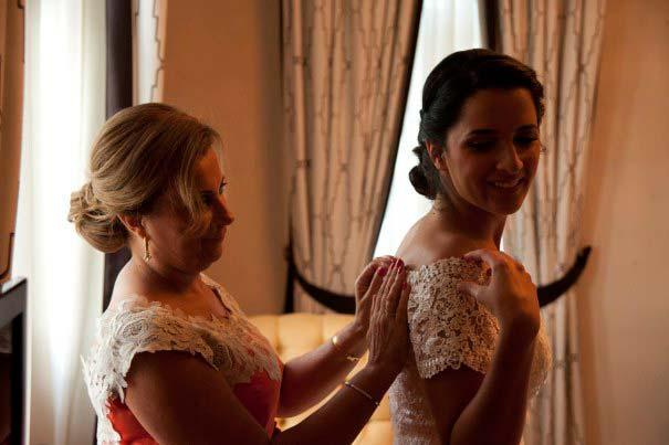 La madre de la novia le ayuda a vestirse antes de su boda