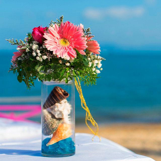Detalle de florero con colores intensos para boda en la playa