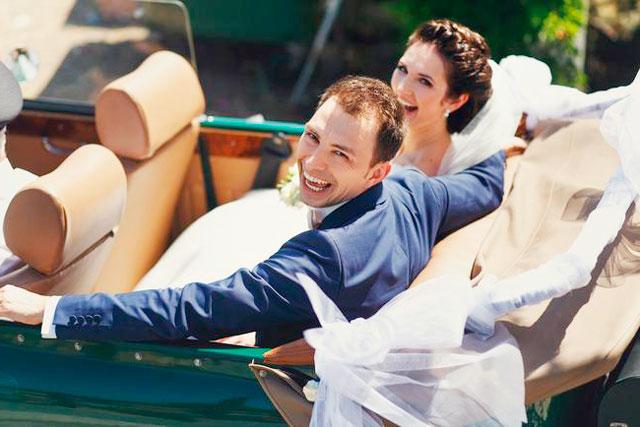 La novia y el novio en unprecioso descapotable el día de su boda